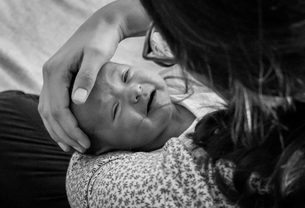 Baby weint Mama streicht liebevoll über seinen Kopf