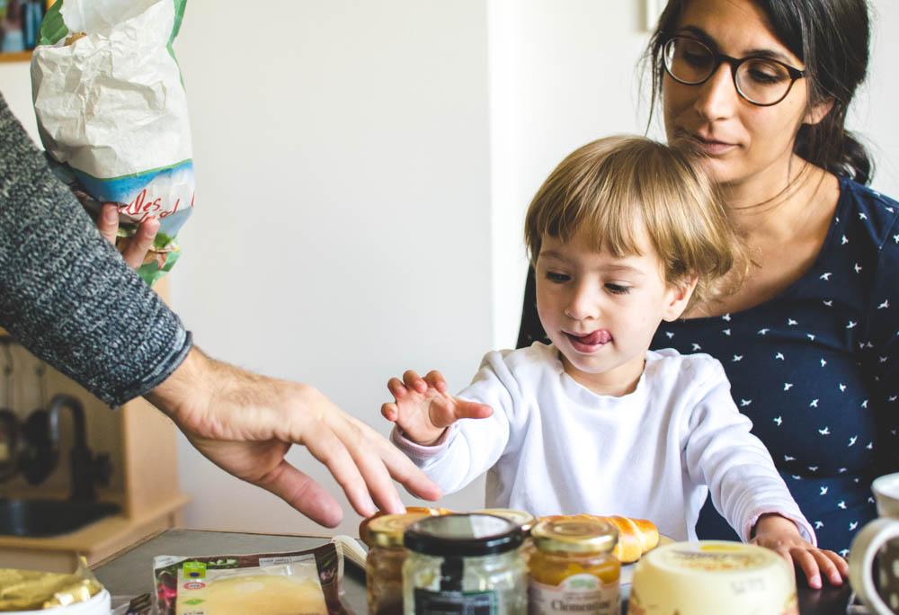 Frühstücken, 2 Jährige leckt sich die Lippen, als Papa eine Laugenstange auf ihren Teller legt, Sitzt auf Mamas schoß