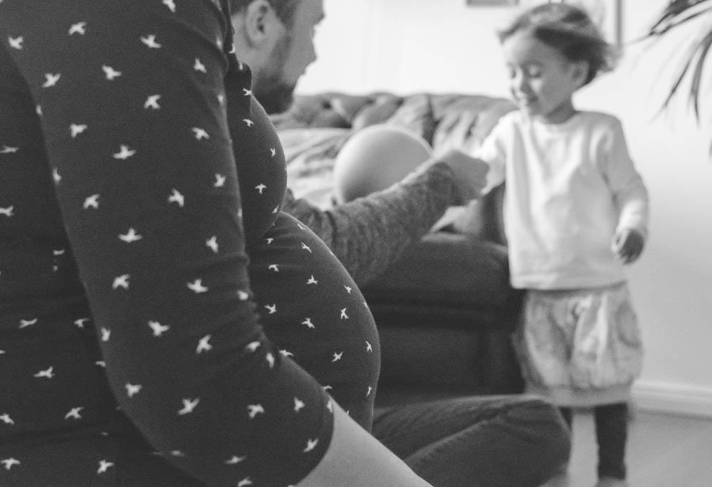 Vordergrung Babybauch hintergrund Vater pustet Tochter mit Luftballon Luft ins Gesicht