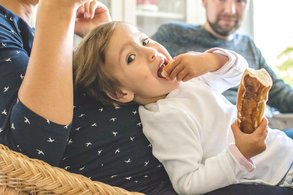 Mädchen & Mama sitzen, Mädchen lehnt sich zurück gegen schwangeren Bauch der Mama, isst dabei Laugenstange
